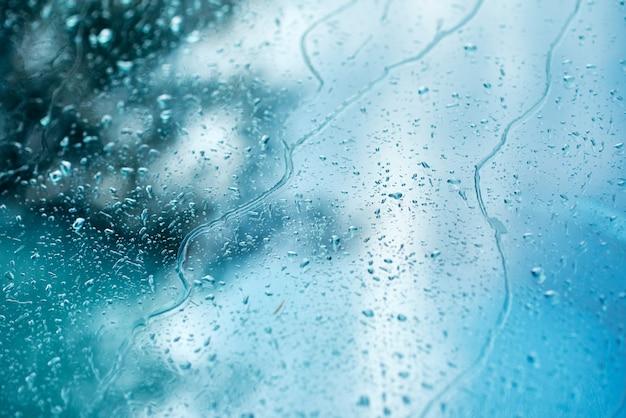 車の窓、抽象的な背景に雨の滴 Premium写真