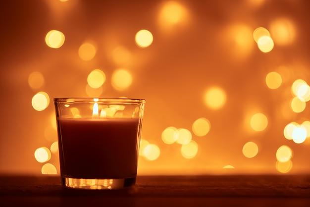 Силуэт горящей свечи с золотыми размытыми огнями Premium Фотографии