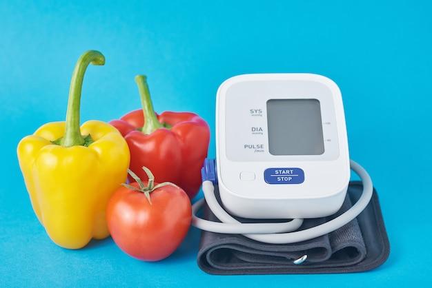 Цифровой тонометр и свежие овощи на синей поверхности Premium Фотографии