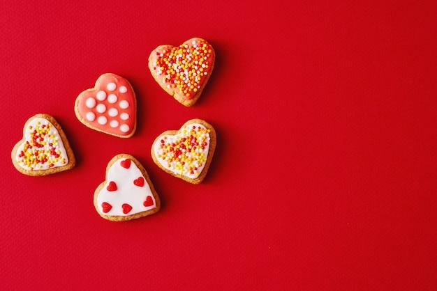 コピースペースと赤い表面にアイシングと艶をかけられたハート形のクッキーで飾られました。バレンタインデーの食べ物のコンセプト Premium写真