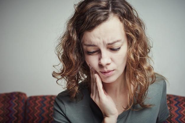 歯痛に苦しんでいる女性。歯の痛みの概念 Premium写真