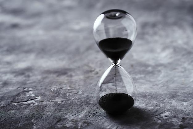 コピースペースで暗い背景に砂時計。時間切れと締め切りの概念 Premium写真