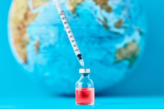Медицинский шприц и ампула с медициной против земного шара. концепция эпидемии, вируса и инфекции человека Premium Фотографии