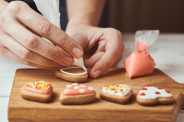 Украшать пряники глазурью. руки женщины украшают печенье в форме сердца, крупным планом Premium Фотографии