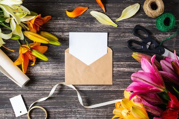 クラフト茶色の封筒と黒い木製の背景の装飾と白い空のシート Premium写真