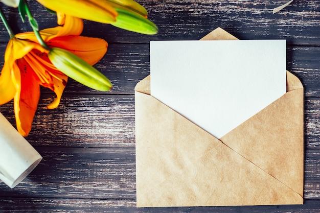 Макет белая открытка и конверт с цветами лилии на деревянном фоне Premium Фотографии