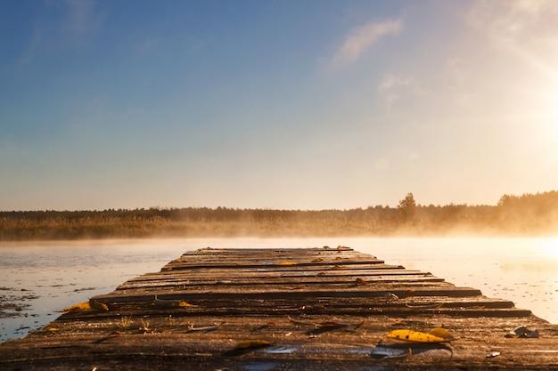 日の出や木の桟橋で川に沈む夕日。 Premium写真