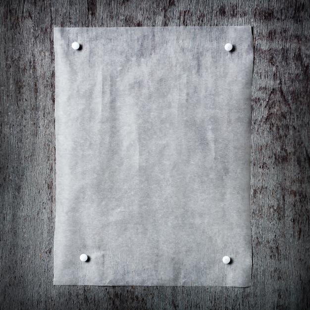 一枚の紙が灰色の木製の背景に固定されています。 Premium写真