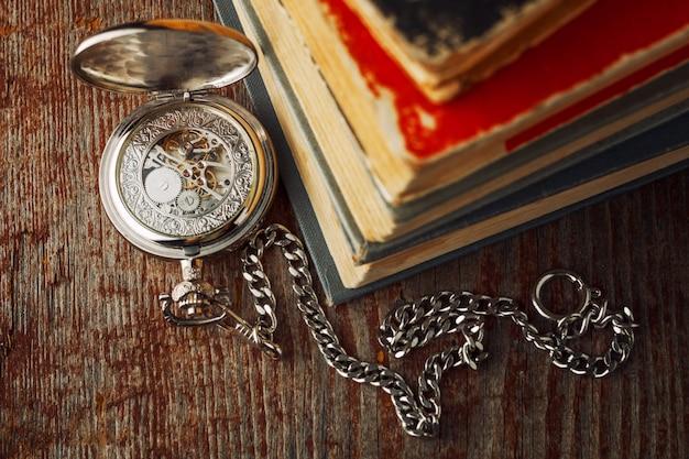 時計と木製の背景上の古い本。 Premium写真
