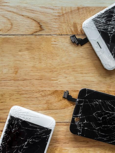 木製の背景にひびの入ったスマートフォンの画面 Premium写真