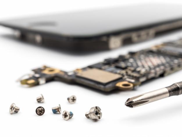スマートフォン部品がぼやけているネジとドライバ Premium写真
