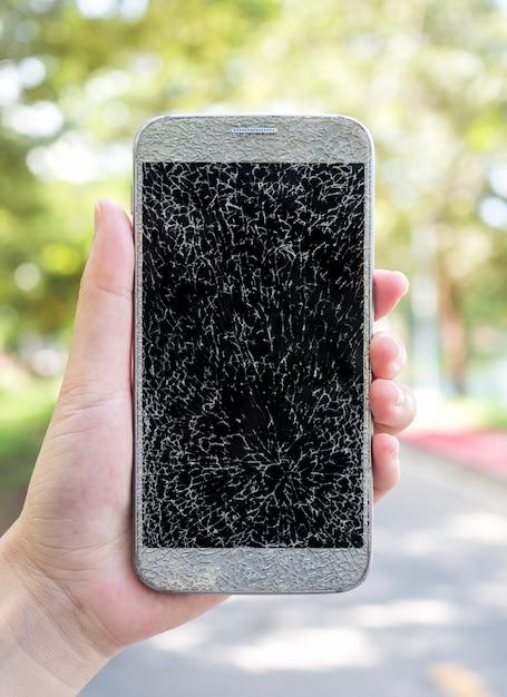 古い壊れてひびの入った画面のスマートフォン Premium写真