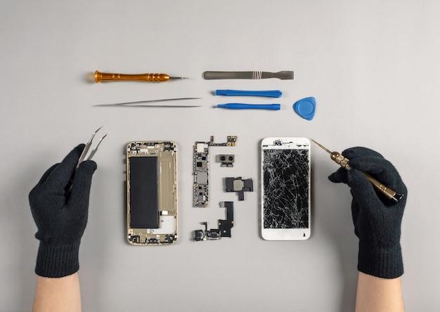 机の上の壊れたスマートフォンを修復する技術者 Premium写真