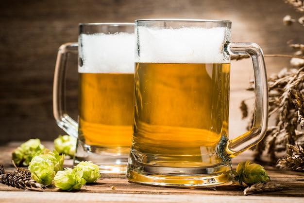 木製のテーブルの上のビールのクローズアップのカップル Premium写真