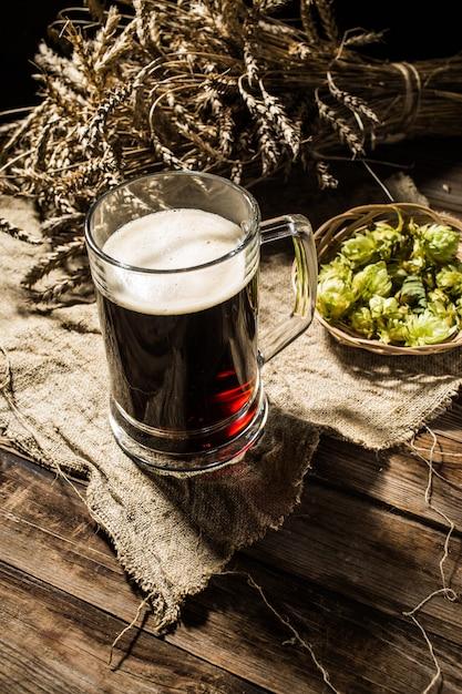 Кружка пива с пшеницей и хмелем на льняной ткани Premium Фотографии