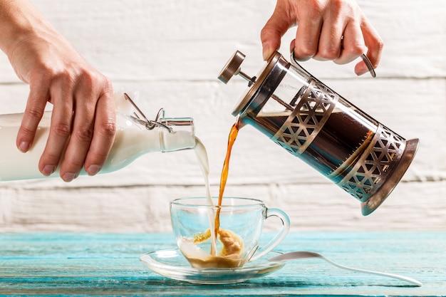 コーヒーとミルクをカップに注ぐ Premium写真