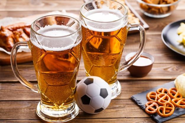 サッカーの試合を観戦するためのテーブルの前菜とビール。 Premium写真
