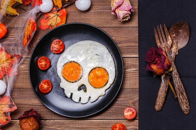 頭蓋骨とフレッシュトマトの形の目玉焼き。ハロウィーンの装飾で朝食します。 Premium写真