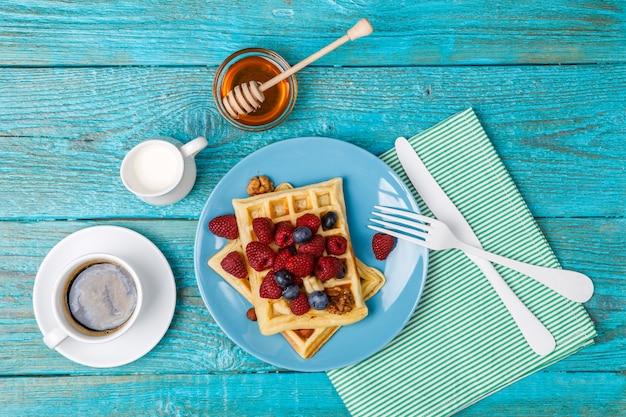 Домашние вафли с малиной и черникой, чашка кофе, молоко и столовые приборы Premium Фотографии