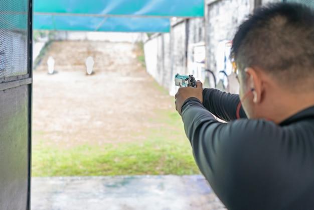 射撃場でターゲットで銃で撃っている男の後姿。 Premium写真