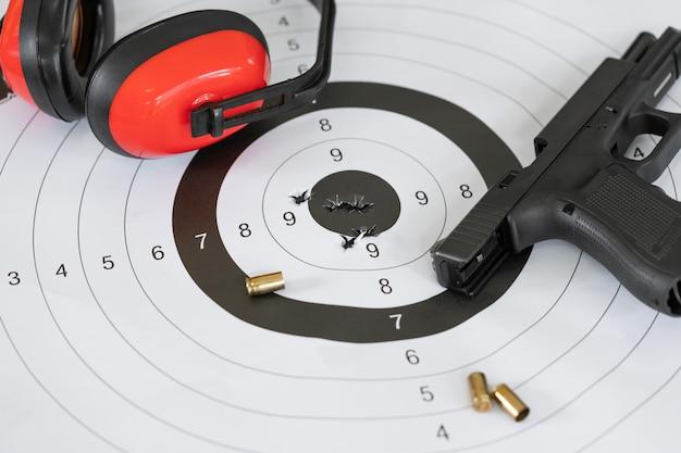 Стрельба по мишени и яблочко с пулевыми отверстиями из автоматического пистолета и патронника пули. Premium Фотографии