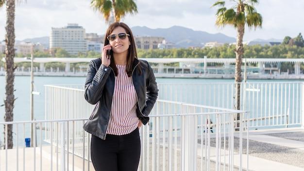 かなり若い女性、マラガ、晴れた日に携帯電話で話している Premium写真