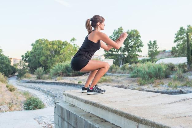公園でスクワットをやっているフィットネス若い女性 Premium写真