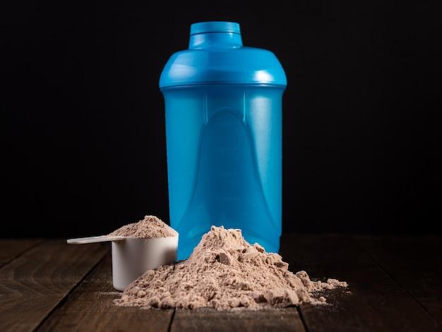 ミルクセーキを準備するために木製のテーブルでホエイプロテインのスクープを測定します。 Premium写真