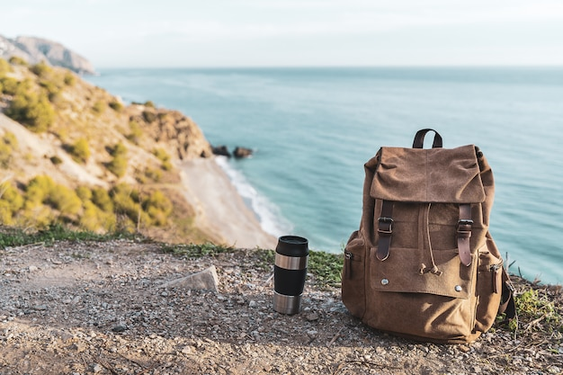Термос рюкзака и кофе с побережьем на заднем плане. концепция исследования и приключений Premium Фотографии