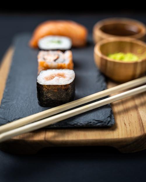 巻き寿司、巻き、うらまき、にぎり、刺身のセットが石板の上で楽しめます。 Premium写真