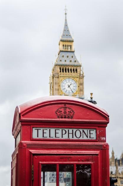 バックグラウンドでビッグベンと伝統的なロンドンの電話ボックス Premium写真