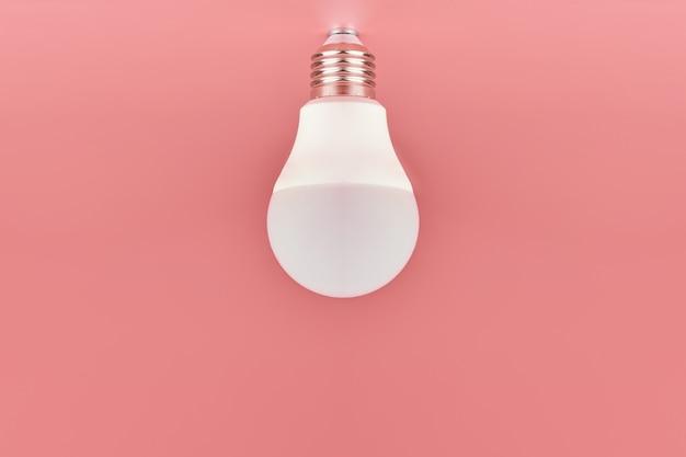 ピンクの背景の省エネ電球 Premium写真