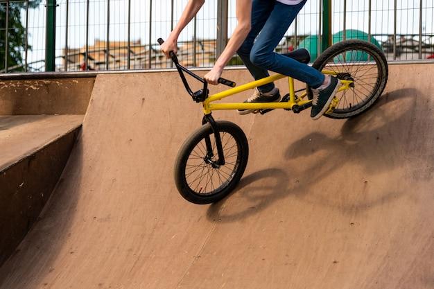 ランプを下りる若いサイクリスト。男はランプから自転車を転がしています。 Premium写真