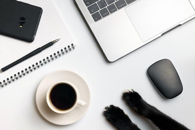 コンピューターのマウス、ラップトップ、コーヒーカップ、携帯電話、ノートブックの近くの猫の足。 Premium写真