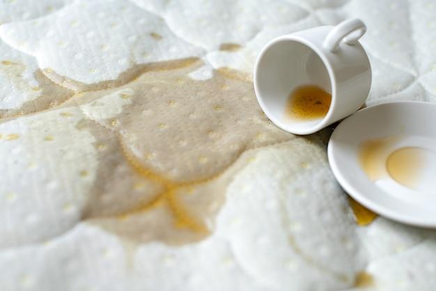 ベッドの上にお茶をこぼした。誤って白いシーツの上の受け皿とカップを落とした Premium写真