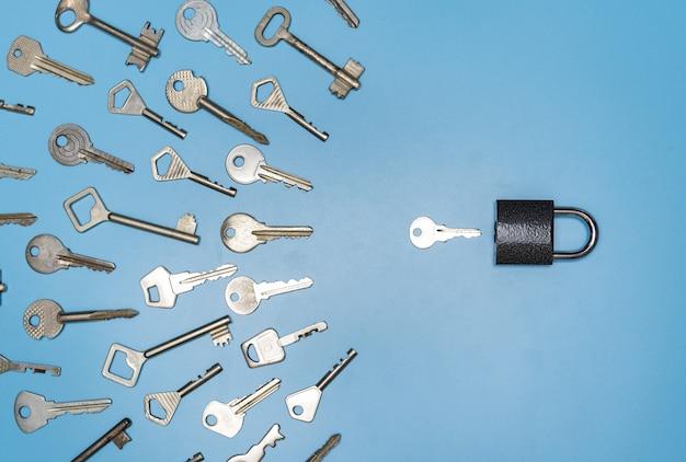 キーピッキングの概念、ロックと異なるアンティークと新しいキー、青い背景 Premium写真