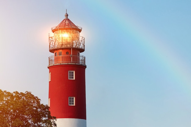 バルチスク港の灯台。美しい虹と標識灯。 Premium写真