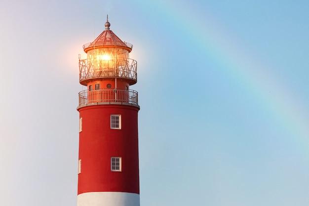 バルチスク港の灯台。美しい虹と標識灯 Premium写真