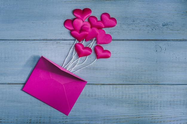 木製の背景上の封筒の上のピンクのサテンハート Premium写真