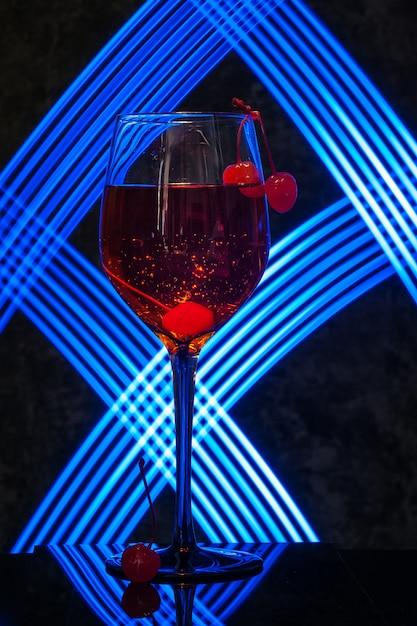 暗闇の中で桜とアペロールスプリッツカクテルのグラス Premium写真