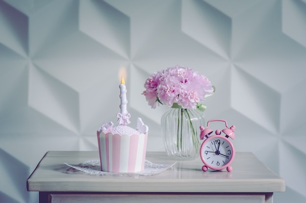 誕生日カップケーキデザートとパーティーのための目覚まし時計とピンクの花 Premium写真