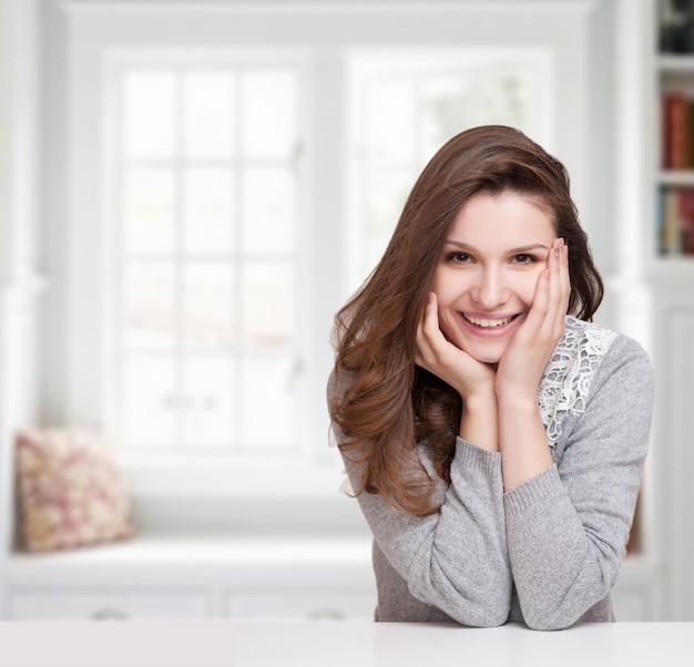 彼女の手に彼女のあごを休んで、カメラを直接見て幸せな笑顔の女性の肖像画を間近します。 Premium写真