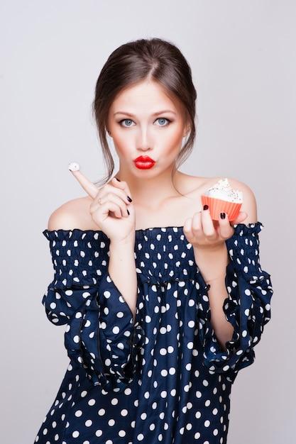 美しい若いレトロなピンナップ女性は甘いケーキの食べ物を食べる Premium写真