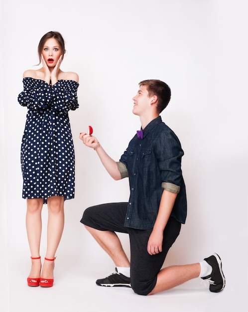 ガールフレンドを提案している彼の膝の上に若い男。 Premium写真