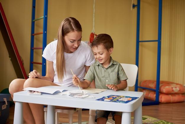 母と息子は部屋の中のテーブルで絵を描きます。 Premium写真