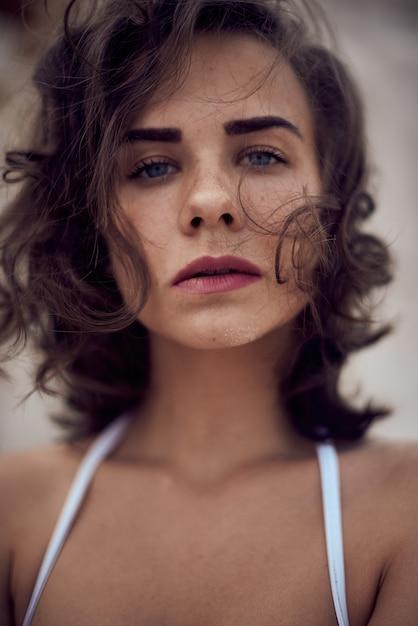 白い砂浜の夏のビーチで横になっているストライプの水着で暗い長い髪の美しい白人日光浴女性モデルの肖像画。上面図 Premium写真