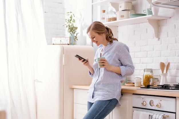 コーヒーマグカップと近代的な家の主催者の台所のテーブルにもたれてスマートフォンを使用して若い女性。電話のメッセージを読んで笑顔の女性。テキストメッセージを入力して幸せなブルネットの少女。 Premium写真