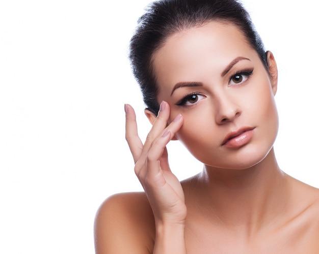 彼女の顔に触れる美しい若い女性 Premium写真