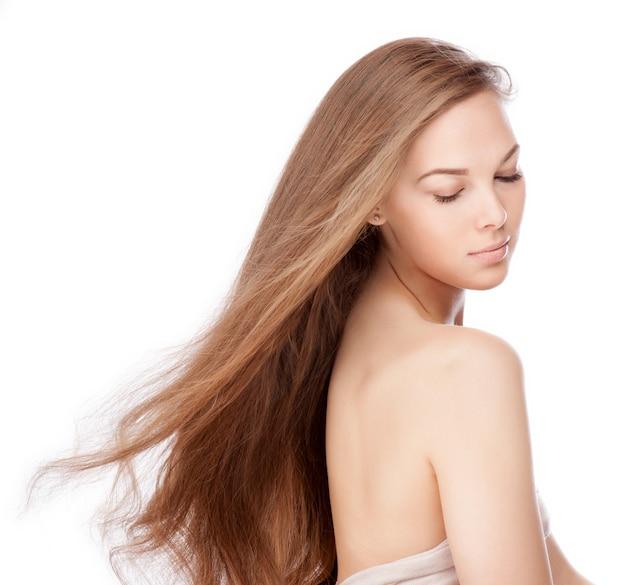 美しい長い茶色の空飛ぶ毛を持つ官能的な若い女性 Premium写真