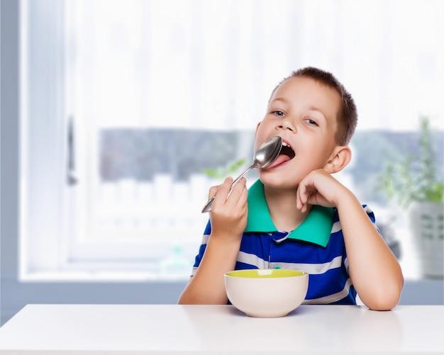 小さな男の子が台所で健康的な朝食を食べる Premium写真